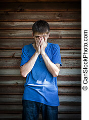 Sad Young Man by the Wooden Wall outdoor