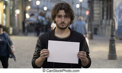 Sad young man holding a white copy space banner on the street