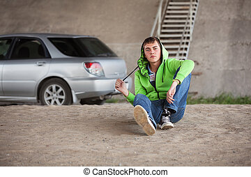 Sad young man in depression sitting on the ground next to his car