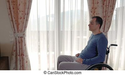 Sad young man in wheelchair looking through the window at...