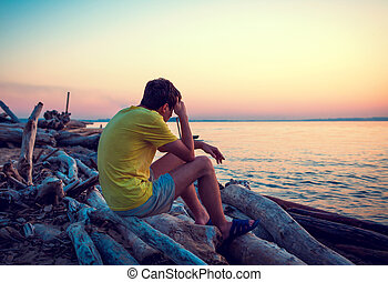 Sad Young Man outdoor - Lonely Young Man sit at Seaside in...