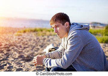 Sad Young Man outdoor - Sad and Lonely Young Man sit on the...