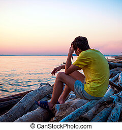 Sad Young Man outdoor - Sad Young Man sit at Seaside in the...