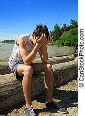 Sad Young Man outdoor - Sad Young Man sit on the Beach with...