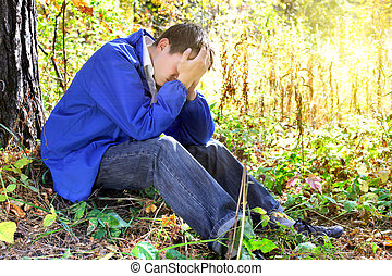 sad young man - sad teenager sitting in the autumn forest...