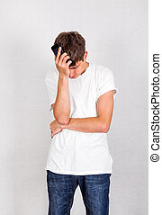 Sad Young Man with a Phone on the White Wall Background
