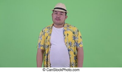 Sad young overweight Asian tourist man giving thumbs down -...
