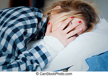 Sad young tired woman lying on the bed