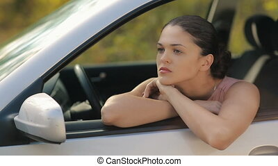 Sad young woman in a car - Road trip car trouble. A young...