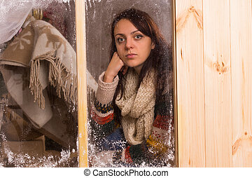 Sad young woman in a winter cabin at Christmas staring glumly through a frosted wooden window with a look of loneliness and longing
