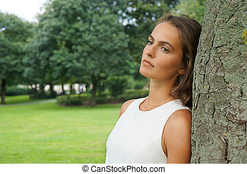 sad young woman leaning against tree gazing absentmindedly...