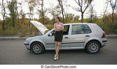 Sad young woman near broken car - Road trip car trouble. A...
