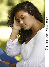 Sad Young Woman Sitting In Park