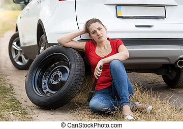 Sad young woman sitting on ground and leaning on spare whheel of broken car