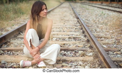 Sad young woman sitting on the railway .