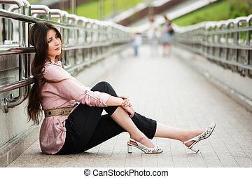 Sad young woman sitting on the sidewalk