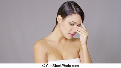 Sad young woman wiping a tear from her eye with a tissue ...