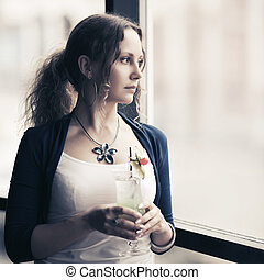 Sad young woman with cocktail looking out the window