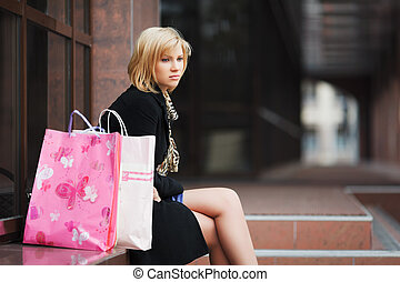 Sad young woman with shopping bags