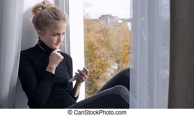 Sad young woman with smartphone sitting on windowsill