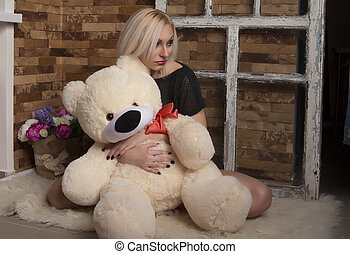 Sad young woman with toy bear in the room