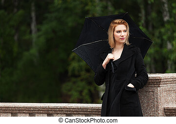 Sad young woman with umbrella in the rain