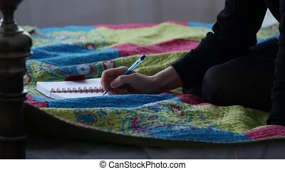 Sad young woman writes in her diary while sitting on a bed....