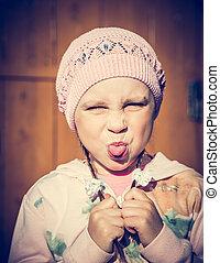 Saddened child against the wall showing tongue. - Saddened ...