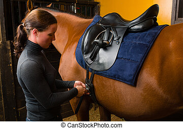Saddle a horse - Woman saddle a horse in the stall