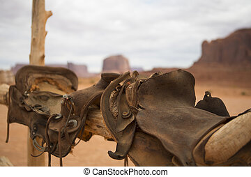 Saddle and wild west - Saddle and red rocks in monument...