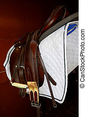 Saddle on a rack in a tack room, horseback riding equipment