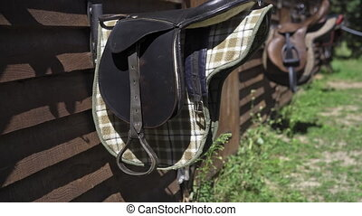 Saddles hang on a wooden pallet wall near the stall ready for sledging on horses with a camera slide down panorama. Riding lessons. Hippotherapy is a concept. High quality 4k footage.