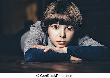 sadly looking boy - Portrait of a calm and sad boy lying on...