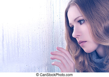sadness girl at the window in the rain