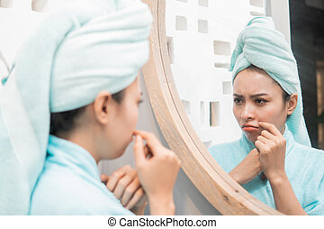 sadness girl with pimple on the cheek when looks to the mirror
