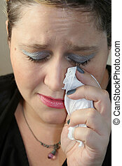 sadness - grieving woman crying with tissue