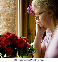 lonely elderly woman is sad sitting by the window