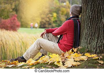 Sadness - Sad man sitting under autumn tree in park