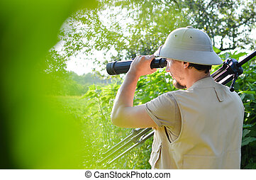 safari tour time: picture of tourist or exploring scientist male in pith helmet having fun observing looking in magnification scope on summer sunny day green woods & sky copy space background portrait