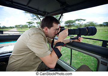 Safari vacation. Professional photographer taking picture on...