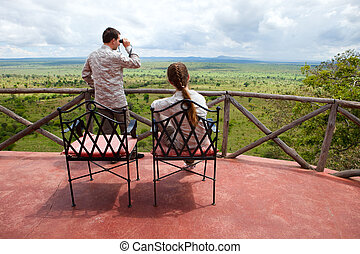 Safari vacation. Young couple in safari clothes observing...
