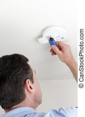 Man carefully replacing 9 volt battery in round white ceiling smoke alarm detector for the safety of his household.