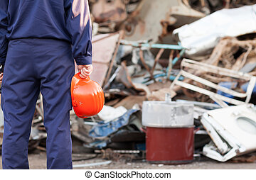 safe recycling - closeup of worker holding helmet standing...