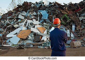 safe recycling - worker standing in front of pile of...