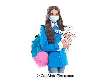 Safe to learn during COVID-19. Little kid wear medical mask holding toy dog. Safe return to school is critical. Student safety. Education during pandemic. Preventing SARS-CoV-2 transmission.