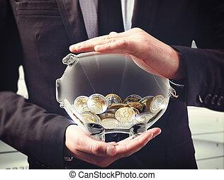Safeguard their earnings - Man holds a transparent piggybank...
