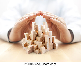 Safety business development concept. Wooden blocks covered by hands.