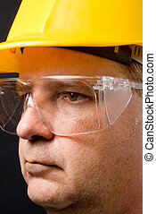 Safety Glasses - A man with a hard hat wearing safety...