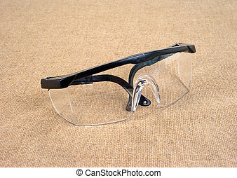 Safety glasses - A pair of used safety glasses on a burlap...