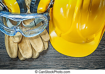 Safety gloves goggles earmuffs hard hat on wooden board